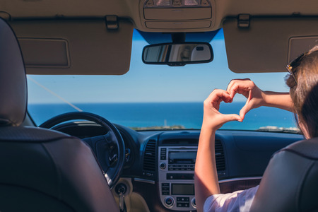 Mädchen, das mit dem Auto auf dem Italien reist und ihre Hände in Form von Herzen hält. Reisen Sie Liebessymbol. Standard-Bild