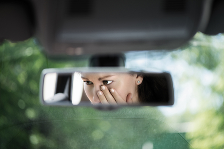 Reflection of young woman with crying eyes covering her face with hands in the car rear view mirror. Concept of an accident on the road or knock down pedestrian