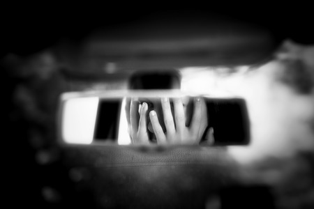 Black and white art picture of young woman with frightened eyes covering her face with hands in the car rear view mirror. Banco de Imagens