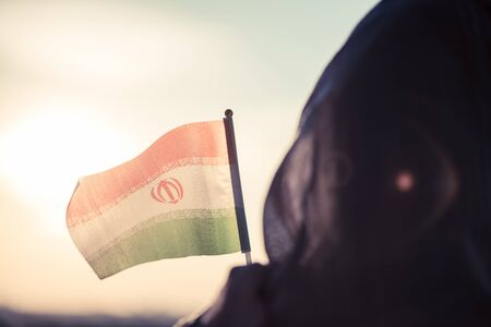 Muslim woman in scarf with Iranian flag at sunset.Concept