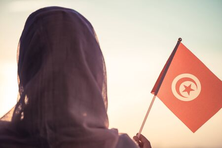 Muslim woman in scarf with Tunisia flag of at sunset.Concept