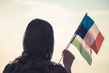 Muslim woman in scarf with  Iranian and French flags of at sunset.Concept