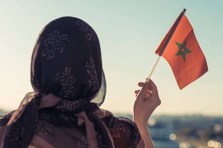 Muslim woman in scarf with Morocco flag of at sunset.Concept Stock Photo