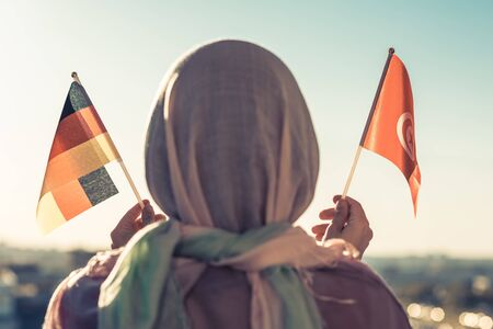 Muslim woman in scarf with Tunisia and Germany flags of at sunset.Concept