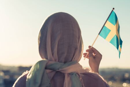 Muslim woman in scarf with Swedish  flag of at sunset.Concept