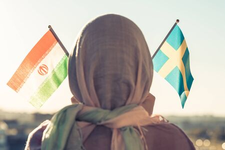 Muslim woman in scarf with Swedish and Iranian flags of at sunset.Concept