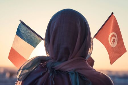 Muslim woman in scarf with Tunisia and French flags of at sunset.Concept