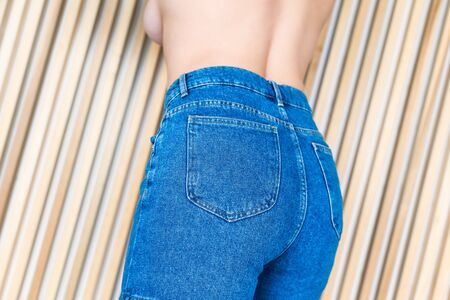 Bottom view on womens buttocks in denim shorts on the background of wooden beams
