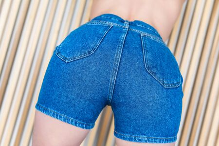 Bottom view on women's in denim shorts on the background of wooden beams