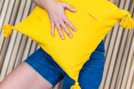 Bottom view on women in the blue denim shorts hugging yellow pillow on the background of wooden beams
