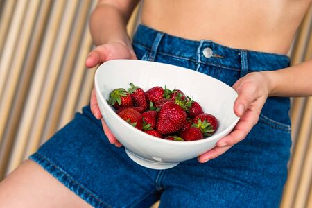 Bottom view on women in denim shorts with ripe strawberry in the bowl on the background of wooden beams Reklamní fotografie
