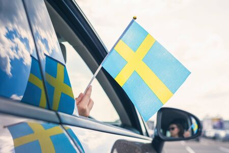 Woman or Girl Holding Swedish Flag from the open car window. Concept