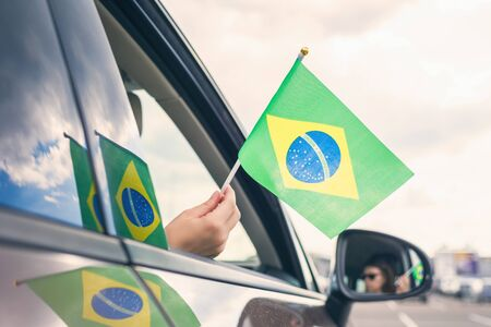 Woman or Girl Holding Flag of Brazil from the open car window. Concept Foto de archivo