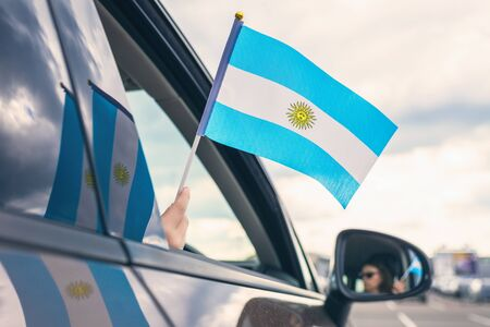Woman or Girl Holding Flag of Argentina from the open car window. Concept Foto de archivo