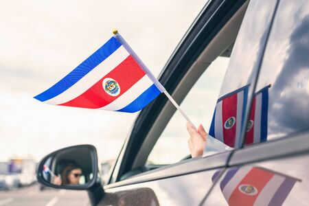 Woman or Girl Holding Flag of Costa Rica from the open car window. Concept