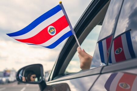 Woman or Girl Holding Flag of Costa Rica from the open car window. Concept Foto de archivo