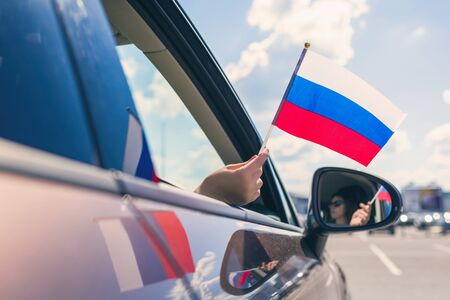Woman or Girl Holding Russian Flag from the open car window. Concept Banque d'images