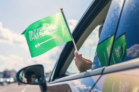 Woman or Girl Holding Saudi Arabia Flag from the open car window. Concept