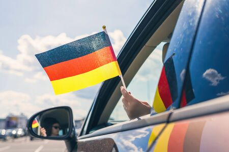 Woman or Girl Holding Germany Flag from the open car window. Concept Banque d'images