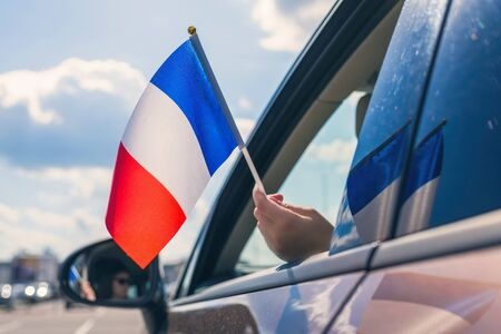Woman or Girl Holding France Flag from the open car window. Concept Foto de archivo