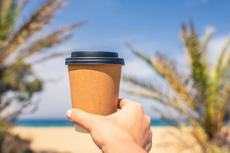Woman's hand with paper cup of coffee on the palm trees background.