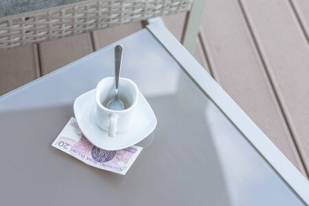 Twenty Polish zloty and empty cup of coffee on a glass table of outdoor cafe. Payment, tip. Banque d'images