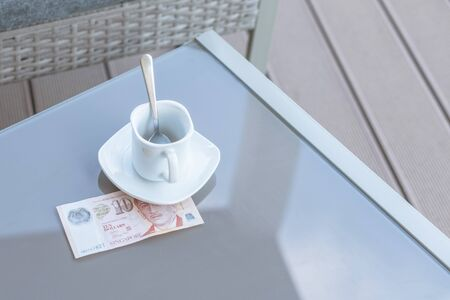 Singapore ten dollars bill and empty cup of coffee on a glass table of outdoor cafe. Payment, tip. Banque d'images