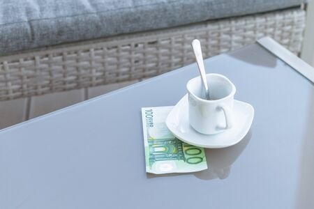 One hundred euro and empty cup of coffee on a glass table of outdoor cafe. Payment, tip. Banque d'images