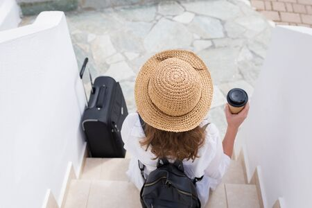 woman with suitcase, straw hat and paper cup of coffee sits on the steps and waits for the owners of the apartment of the resort town. Individual traveler. Check - in