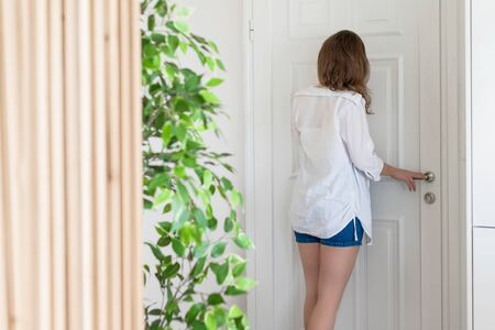 woman in shirt and shorts looking in peephole door when somebody rings the doorbell