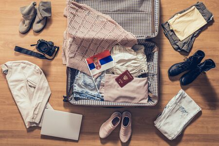 Woman's clothes, laptop, camera, russian passport and flag of Serbia lying on the parquet floor near and in the open suitcase. Travel concept