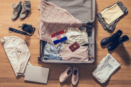 Woman's clothes, laptop, camera, russian passport and flag of Croatia lying on the parquet floor near and in the open suitcase. Travel concept