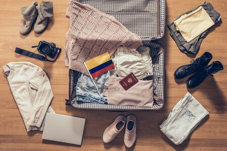 Woman's clothes, laptop, camer, russian passport and flag of Colombia lying on the parquet floor near and in the open suitcase. Travel concept