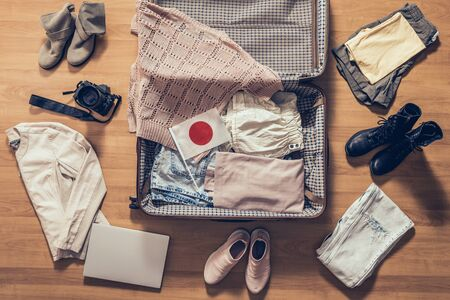Woman's clothes, laptop, camera and flag of Japan lying on the parquet floor near and in the open suitcase. Travel concept 版權商用圖片