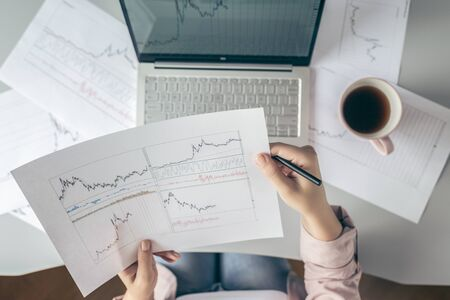 Top view. Young business woman sitting at table with cup of coffee and working on the laptop with graphics and charts printed on the paper.