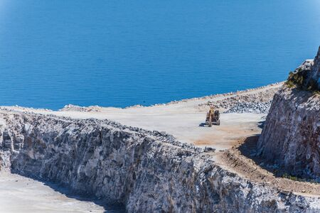 Aerial view of opencast mining quarry with one machinery on the blue sea background