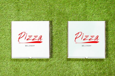 Two white box with an inscription of pizza on the grass. Discount or summer promotion concept. Second pizza for free.Top view