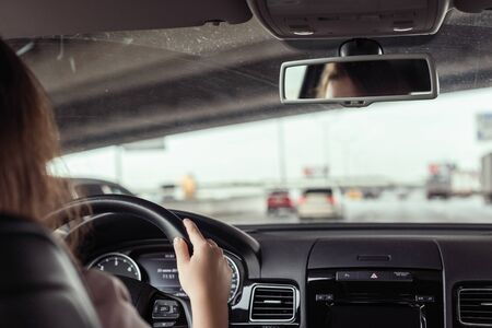 woman is driving on the highway under the bridge. View from the back seat of the car Stock Photo