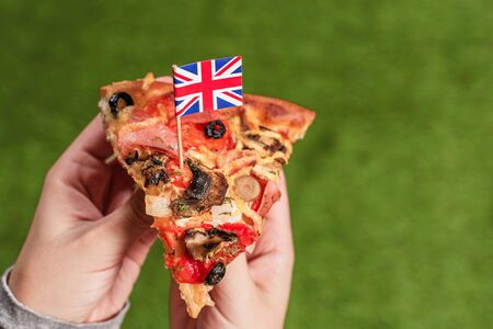 A slice of pizza in female hands with English flag in the form of a toothpick. Lunch on the green grass. Great Britain. Concept 写真素材