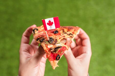 A slice of pizza in female hands with Canadian flag in the form of a toothpick. Lunch on the green grass. Canada. Concept 写真素材