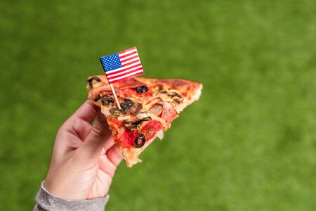 A slice of pizza in female hands with american flag in the form of a toothpick. Lunch on the green grass. Concept