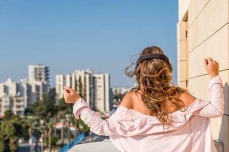 woman in a pink shirt on the balcony dancing and listening music in a headphones against the city background