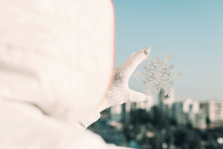 Woman in a jacket and knitted gloves holding huge sparkling snowflake on the town background. Winter and Christmas concept.