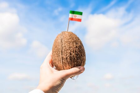 Tropical coconut with Iranian flag in the form of a toothpick in female hands. Tourist from Iran on vacation. Travel concept