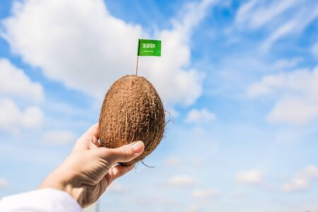 Tropical coconut with Saudi Arabia flag in the form of a toothpick in female hands. Travel concept