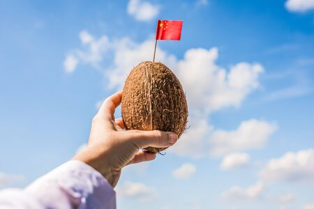 Tropical coconut with Chinese flag in the form of a toothpick in female hands. Travel concept.  Tourism in China 写真素材