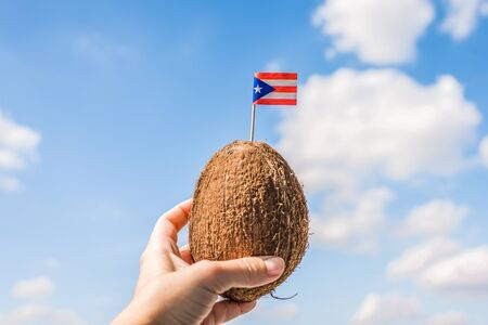 Tropical coconut with the Puerto-Rico flag in the form of a toothpick in female hands. Travel concept.