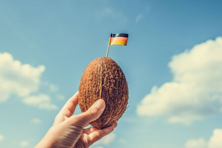 Tropical coconut with Germany flag on the toothpick in female hands. Deutsch tourist on vacation.  Travel concept