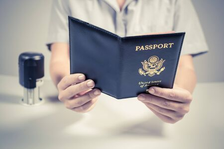 Immigration and passport control at the airport. woman border control officer puts a stamp in the US passport of american citizen. Concept