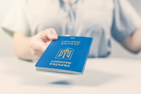 Immigration and passport control at the airport. woman border control officer with Ukrainian passport. Concept 版權商用圖片